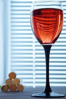Bicchiere di vino rosso e pila di tappi di sughero sullo sfondo