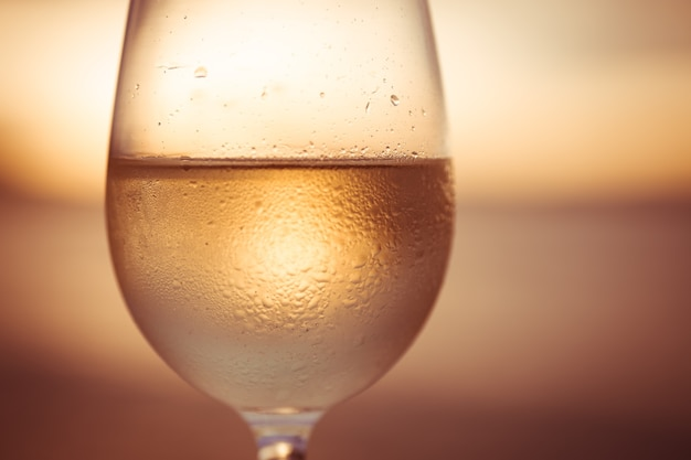 Bicchiere di vino bianco al tramonto con cielo drammatico