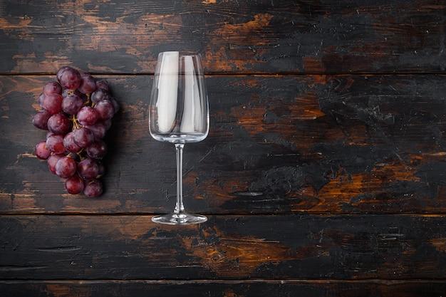 Bicchieri da vino con set di uva, sul vecchio tavolo in legno scuro, vista dall'alto laici piatta