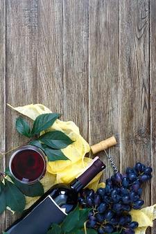 Bicchieri da vino con vino rosso, bottiglia, cavatappi, uva blu, foglie su un tavolo di legno.