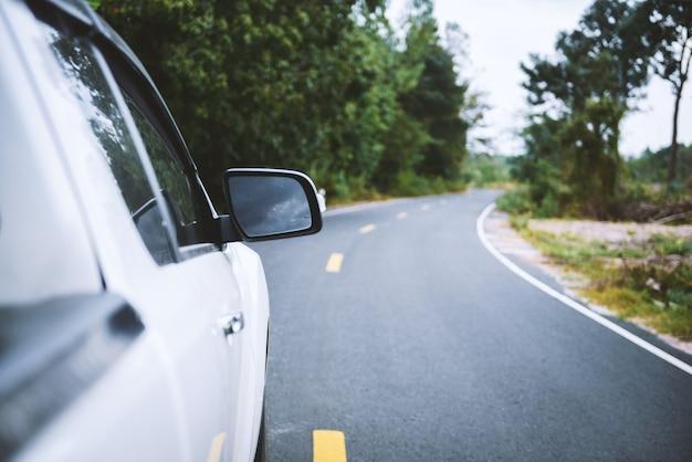 Lo specchietto retrovisore di un'auto con strada naturale.