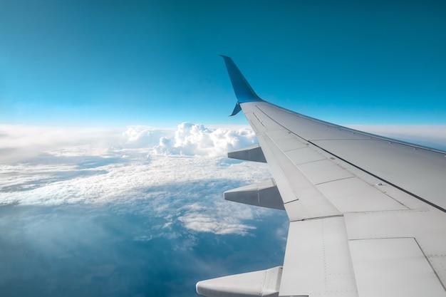 Un'ala di un moderno aereo passeggeri sopra le nuvole. trasporto internazionale di merci, viaggi aerei, trasporti. copia spazio.