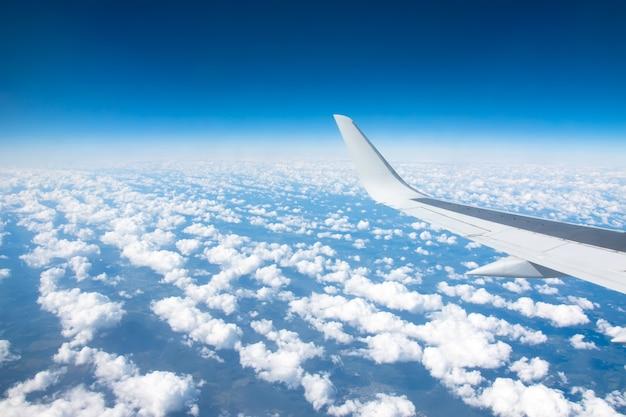 Vista dell'ala dell'aeroplano su un winglets e motore a reazione, soffici nuvole sullo skyline durante la scalata del livello di volo.