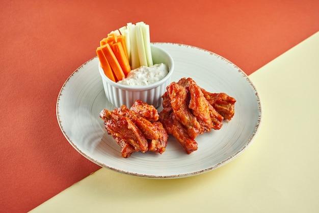 Ali in salsa barbecue con salsa bianca e carote, cetriolo in un piatto bianco su superficie colorata.
