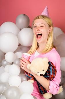 Strizza l'occhio la donna con il cappello da festa festeggia il compleanno. la ragazza sorridente in pigiama celebra il pigiama party