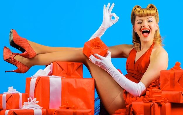 Donna che fa l'occhiolino in abito rosso, acconciatura retrò con scatole regalo mostra un gesto ok su sfondo blu blue