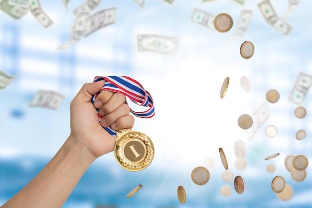 Affari del vincitore. uomo d'affari che tiene moneta d'oro dopo aver vinto il mercato della concorrenza dal reddito in denaro alla sua squadra.