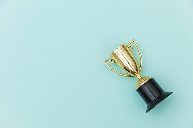 Vincitore o campione coppa trofeo d'oro isolato su sfondo colorato pastello blu Foto Premium