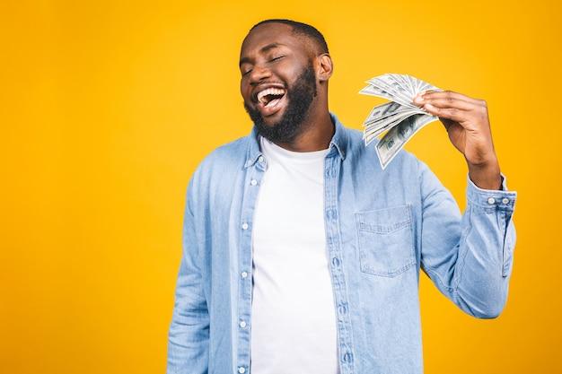 Vincitore! giovane uomo afroamericano ricco in banconote in dollari casuali dei soldi della tenuta della maglietta con la sorpresa