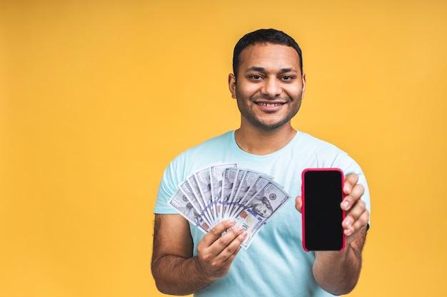 Vincitore! giovane uomo di colore indiano afroamericano felice ricco in banconote da un dollaro di denaro con sorpresa isolate su sfondo giallo muro. utilizzo del telefono cellulare. spazio per la copia dello schermo.