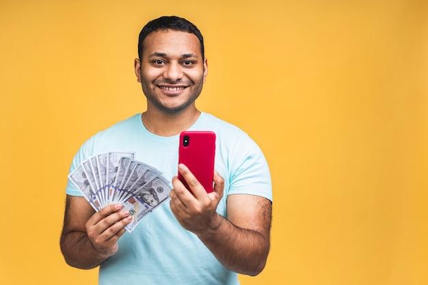 Vincitore! giovane uomo di colore indiano afroamericano felice ricco in banconote da un dollaro di denaro con sorpresa isolate su sfondo giallo muro. utilizzo del telefono cellulare.