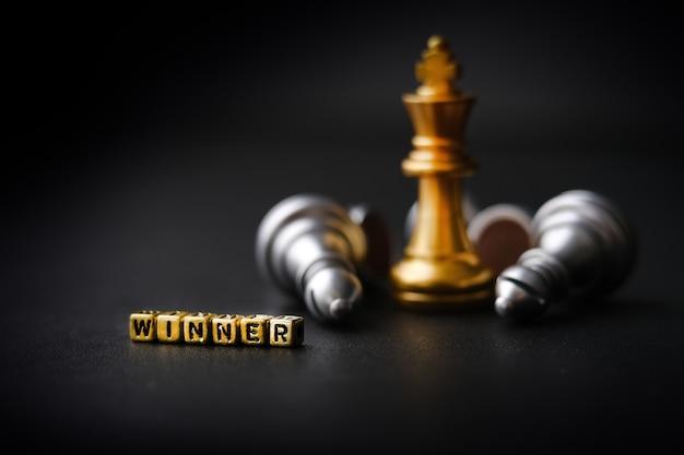 Il business concept vincente: concorrenza e management. un pezzo degli scacchi d'oro su uno sfondo scuro. vincitore di parole. copia spazio per il testo. formato orizzontale