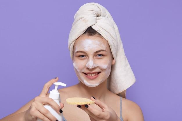 Accattivante signora avvolta in un asciugamano che tiene la bottiglia dell'erogatore, premendo per ottenere la crema per la procedura cosmetica