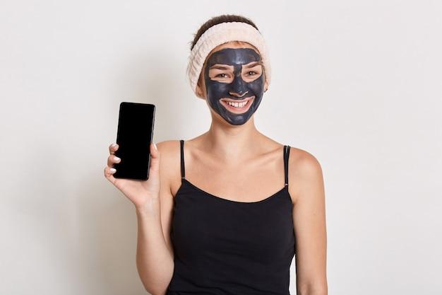 Donna sorridente accattivante con maschera cosmetica nera sul viso, tenendo il cellulare con schermo vuoto