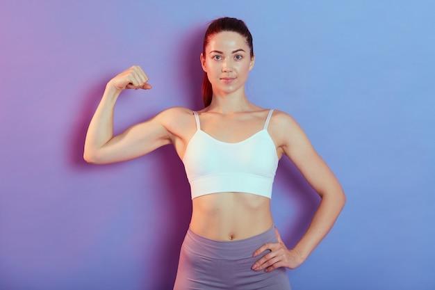 Giovane donna accattivante che mostra i muscoli, tiene una mano sul fianco, guarda la telecamera con un'espressione facciale sicura, indossa una canotta bianca e leggins grigi, posa contro il muro colorato.