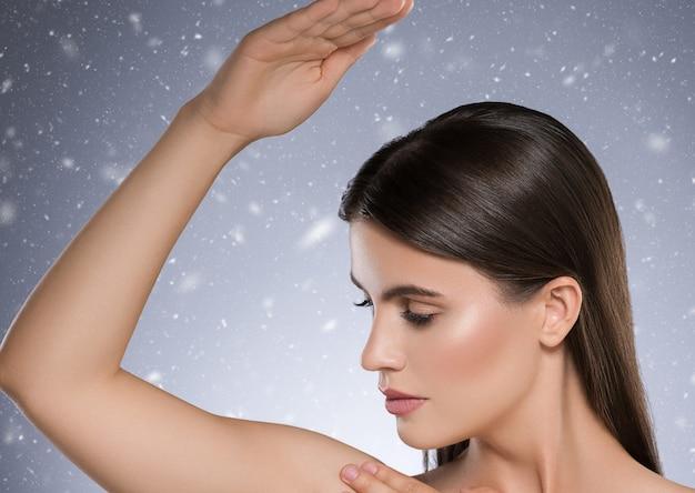 Ascella invernale mano sul concetto di deodorante per la pelle pulita di depilazione della donna. colpo dello studio. colore di sfondo.