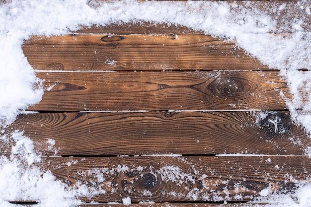 Sfondo invernale. plancia di legno vuota con bordo innevato, copia spazio per il testo tavolo in legno. per l'esposizione del prodotto mock up di natale