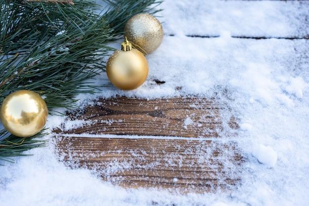 Sfondo invernale. tavola di legno vuota con bordo innevato con ramo di pino e decorazione della palla di natale, spazio per copiare per l'esposizione del prodotto mock up di natale