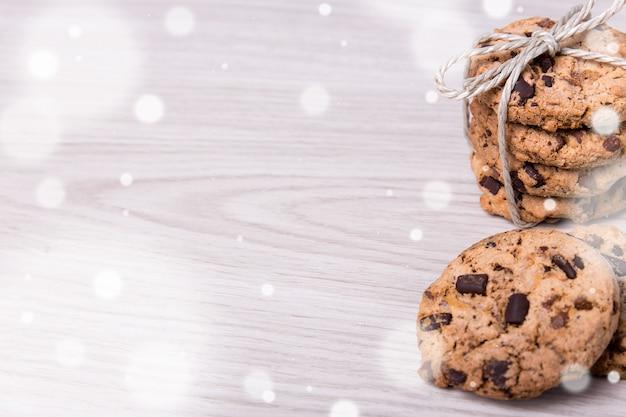 Sfondo invernale biscotti con scaglie di cioccolato appena sfornati e spazio copia su sfondo tavolo in legno