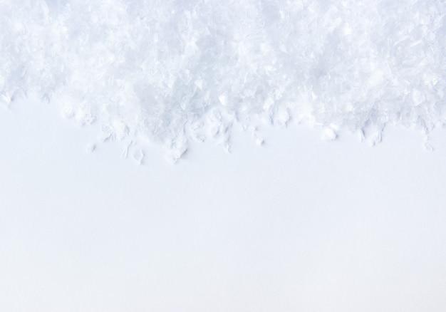 Sfondo invernale pezzi di ghiaccio e neve su uno sfondo bianco con vista dall'alto dello spazio della copia