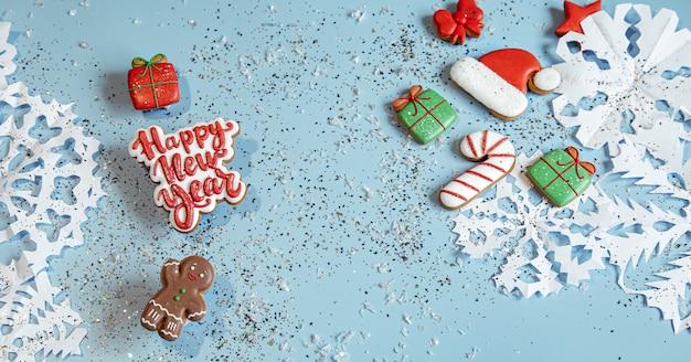 Sfondo invernale con decorato con glassa di pan di zenzero, fiocchi di neve e coriandoli. felice anno nuovo e concetto di natale.