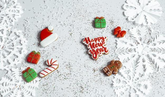 Sfondo invernale con decorato con glassa pan di zenzero, fiocchi di neve e coriandoli vista dall'alto. felice anno nuovo