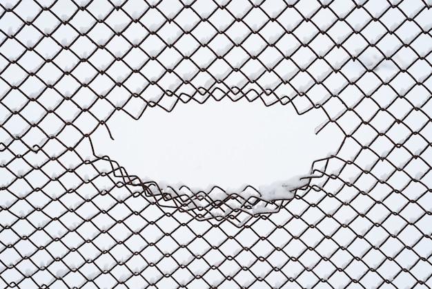 Sfondo invernale con cornice ovale e copia spazio per il testo. astrazione in un ambiente urbano. gap in una rete di recinzione metallica