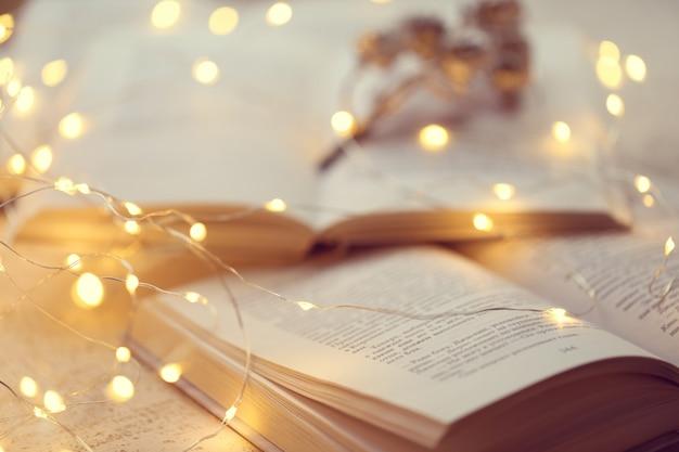 Libri invernali. lettura accogliente invernale. macro pagine e fuoco molle della ghirlanda brillante. mood accogliente. stagione invernale