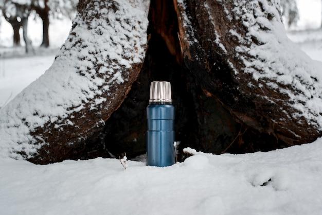 Campeggio invernale nel concetto di foresta. thermos in piedi sullo sfondo di un vecchio albero. borraccia sottovuoto da viaggio