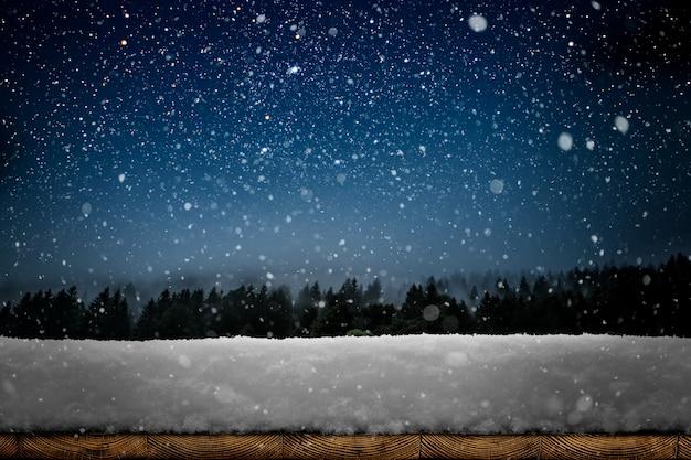 Uno sfondo di natale invernale con neve sul legno