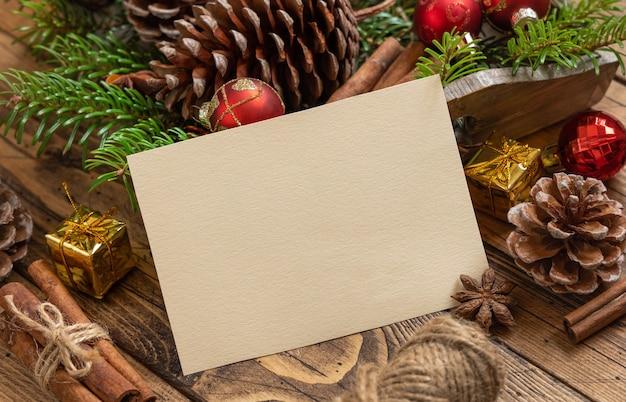 Composizione di natale invernale con una carta bianca su un tavolo di legno vicino modello di biglietto di auguri di natale e capodanno con rami di abete, pigne e decorazioni natalizie. modello di vacanza