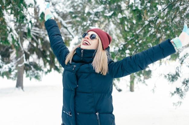 Inverno, natale, emozioni, persone, stile di vita e concetto di bellezza - ritratto all'aperto della ragazza di natale. inverno donna che soffia neve in un parco. fiocchi di neve volanti. giorno soleggiato. retroilluminato. buon umore