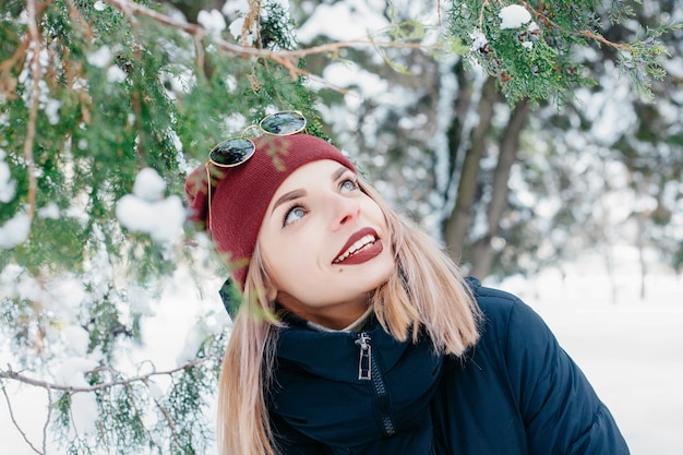 Inverno, natale, emozioni, persone, stile di vita e concetto di bellezza - ritratto all'aperto della ragazza di natale. inverno donna che soffia neve in un parco. fiocchi di neve volanti. giorno soleggiato. buon umore