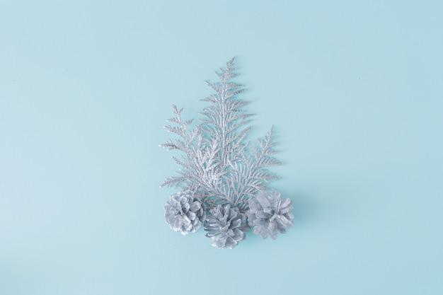 Inverno e natale sfondo festivo. rami argentati di thuja e pigne su sfondo blu