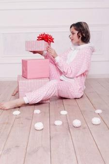 Inverno, natale, vacanze, dolci, compleanno, celebrazione e concetto di bambini - pigiama carino bambina con i dolci che si siedono sul pavimento, concetto di infanzia felice. regali ragazza, cane morbido, bolle di sapone.