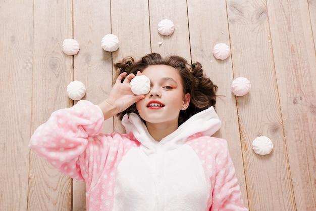 Inverno, natale, vacanze, dolci, compleanno, celebrazione e concetto di bambini: pigiama carino per bambina con dolci seduti sul pavimento, concetto di infanzia felice. regali ragazza, cane morbido, bolle di sapone.