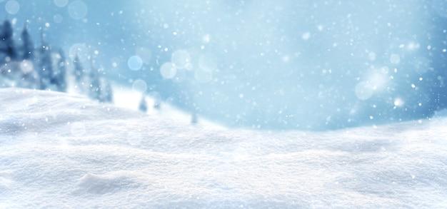 Sfondo di neve invernale e natalizia con cumuli di neve e foresta sfocata innevata.