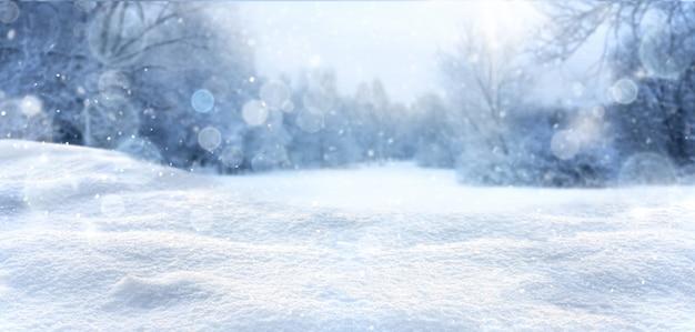 Sfondo innevato invernale e natalizio con cumuli di neve e foresta sfocata innevata. paesaggio invernale freddo con spazio libero.