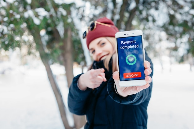 Inverno, natale, tecnologie, persone, stile di vita e concetto di bellezza: messaggio completato con pagamento sullo schermo di un telefono cellulare. donna che mostra il suo telefono cellulare. inverno donna che soffia neve in un parco.