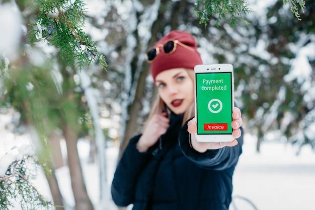 Inverno, natale, tecnologie, persone, stile di vita e concetto di bellezza: messaggio di pagamento completato sullo schermo di un telefono cellulare. donna che mostra il suo telefono cellulare. inverno donna che soffia neve in un parco.