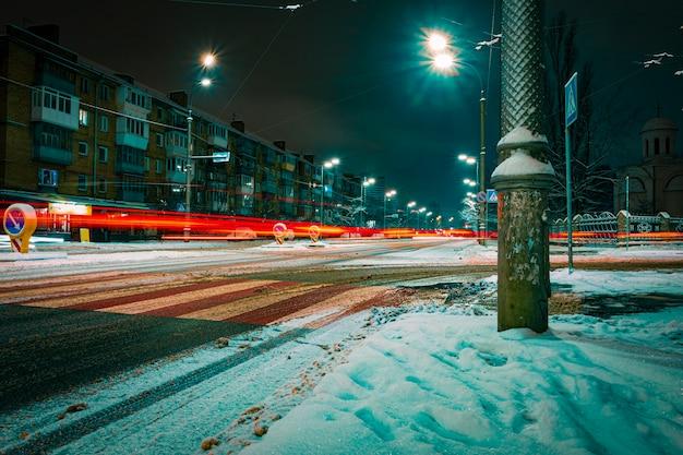 Paesaggio urbano invernale con luci notturne. strada innevata di una città moderna