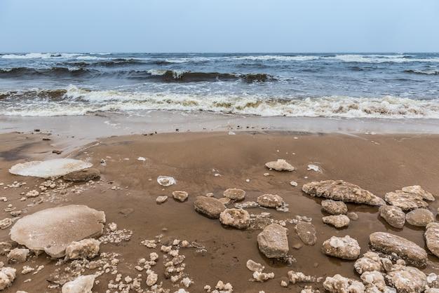 La fredda spiaggia invernale del mar baltico è innevata e ci sono grandi onde nel mare, a saulkrasti in lettonia