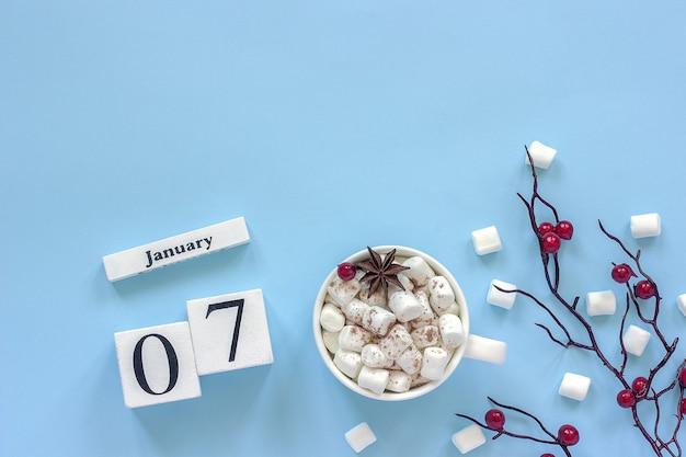 Composizione invernale. cubi calendario in legno bianco. tazza di cacao, marshmallow e ramo decorativo con bacche rosse su sfondo blu vista dall'alto spazio per la copia piatta