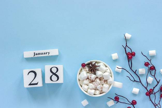 Composizione invernale. cubi calendario in legno bianco. dati 28 gennaio tazza di cacao, marshmallow e ramo decorativo con bacche rosse su sfondo blu vista dall'alto piatto spazio copia laici