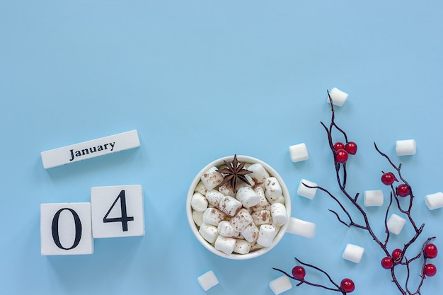 Composizione invernale. cubi calendario in legno bianco. dati 4 gennaio. tazza di cacao, marshmallow e ramo decorativo con bacche rosse su sfondo blu vista dall'alto spazio di copia piatta