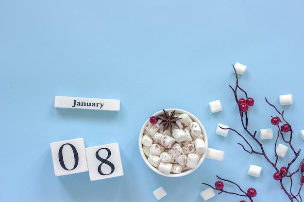 Composizione invernale. cubi calendario in legno bianco. dati 8 gennaio. tazza di cacao, marshmallow e ramo decorativo con bacche rosse su sfondo blu vista dall'alto spazio di copia piatta