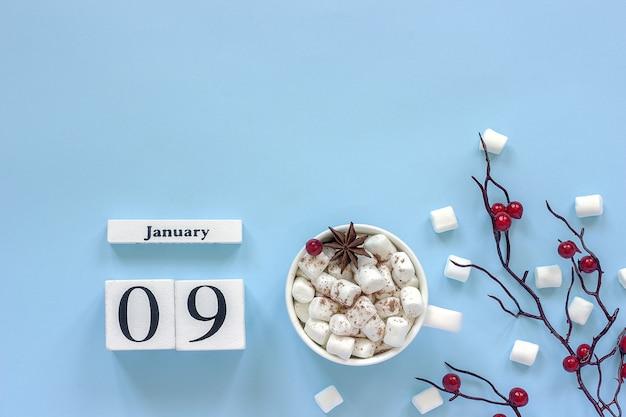 Composizione invernale. cubi calendario in legno bianco. dati il 9 gennaio. tazza di cacao, marshmallow e ramo decorativo con bacche rosse su sfondo blu vista dall'alto spazio di copia piatta