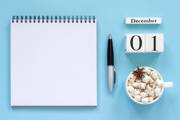 Composizione invernale. calendario in legno 1 dicembre tazza di cacao con marshmallow e anice stellato, blocco note vuoto