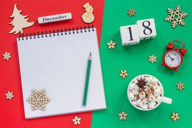 Composizione invernale. calendario in legno 18 dicembre tazza di cacao con marshmallow, blocco note aperto vuoto