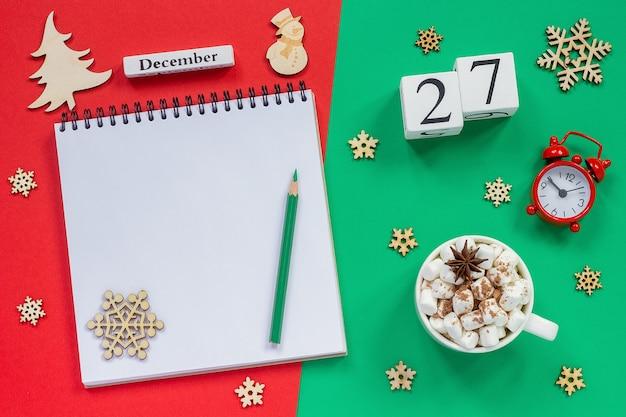Composizione invernale. calendario in legno 27 dicembre tazza di cacao con marshmallow, blocco note aperto vuoto con matita, fiocco di neve, sveglia su sfondo rosso e verde. vista dall'alto mockup piatto
